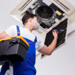Double Check Worker repairing ceiling air conditioning unit