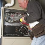 Double Check Repairman servicing or repairing basement furnace unit