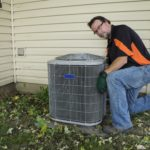 Repairman Cleaning Outside Air Conditioner Unit Grill